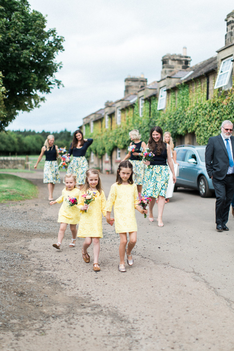 Bridesmaids walking to the threshing hall ceremony room at doxford barns