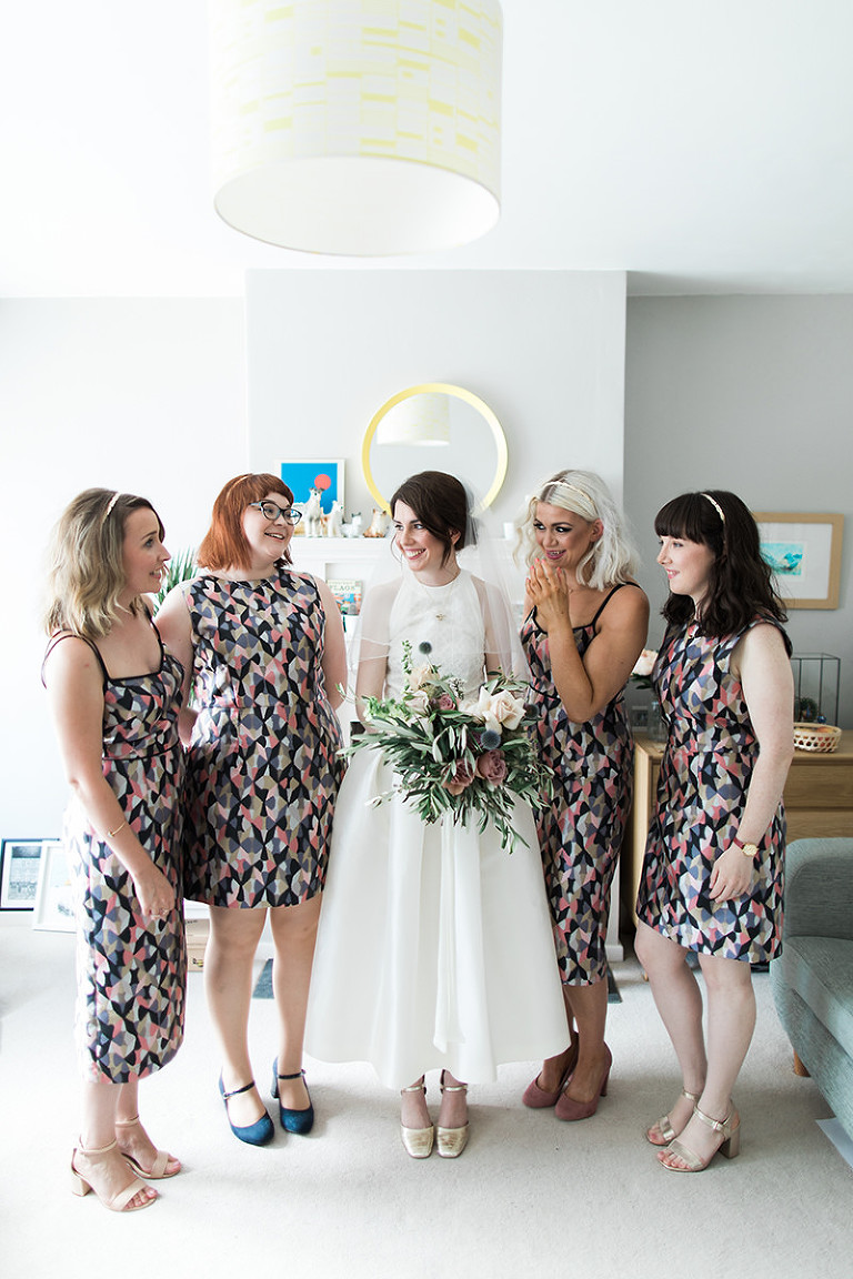 a photo of a bride and bridesmaids indoors in geometric patterned dresses
