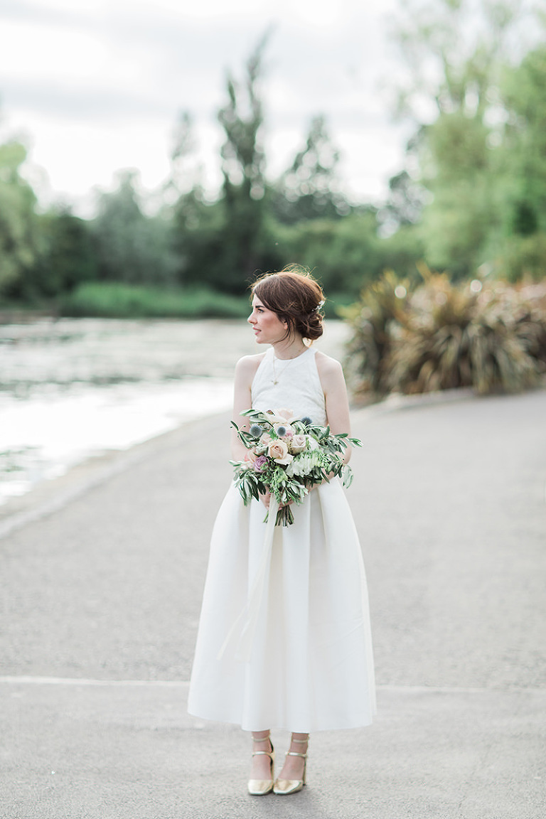 a photo of a bride wearing a two piece wedding outfit outside Wylam brewery